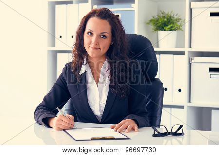 Young Businesswoman Sitting Behind The Desk In The Office And Writes, Toned.