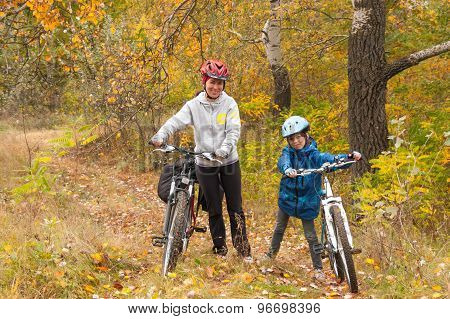 Happy family on bikes cycling outdoors, smiling active mother with kid on bicycles having fun