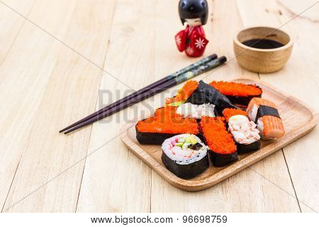 Japanese Sushi Traditional Food On Wooden Plate With Kokeshi.