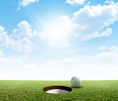 stock photo of manicured lawn  - A view of a perfectly manicured golf putting green and hole with a ball on the edge in the daytime on a blue sky background - JPG