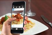 stock photo of meatball  - hand holding smartphone against close up of spaghetti and meatballs with red wine - JPG