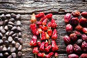 stock photo of pine nut  - the figure of the pine nuts dry red peppers and dogrose on wooden background close - JPG