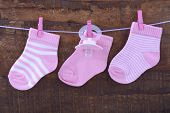 picture of pegging  - Its a Girl Pink Baby Socks and dummy pacifier hanging from pegs on a line against rustic dark wood background - JPG