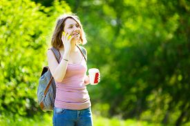 picture of takeaway  - Happy young caucasian woman talking on the phone holding a takeaway coffee cup and smiling - JPG