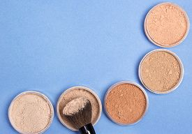 pic of semi-circle  - Semi circle row of jars filled with loose cosmetic powder different shades and makeup brush top view - JPG