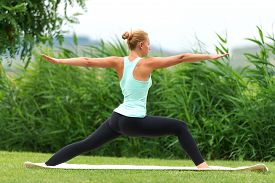 stock photo of virabhadrasana  - Yoga virabhadrasana II warrior pose by woman - JPG