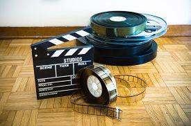 pic of mm  - 35 mm cinema movie clapper board and film reels in background on wooden floor - JPG