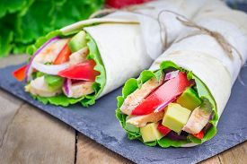 stock photo of sandwich wrap  - Tortilla wraps with roasted chicken fillet avocado tomato onion and puprika - JPG