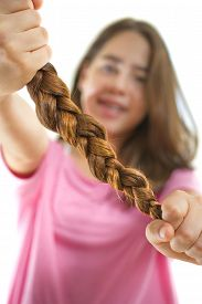 stock photo of generous  - Teenage girl in pink donating her hair to cancer patients - holding her former ponytail after a haircut generously donating her long hair for making wigs for cancer patients who lost their hair ** Note: Shallow depth of field - JPG