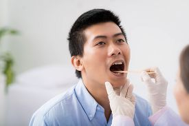 pic of tongue  - Doctor examining throat of patient with tongue depressor - JPG