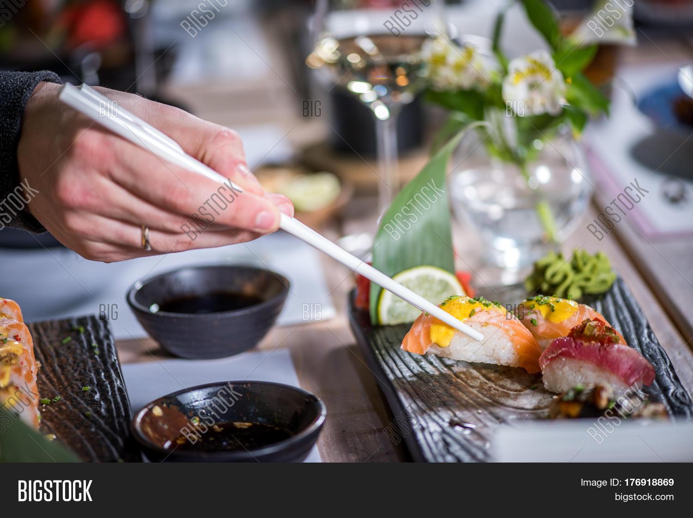 hands eat sushi chopsticks friends image photo bigstock. Black Bedroom Furniture Sets. Home Design Ideas