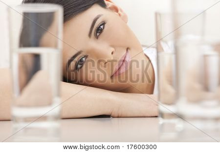 Studio portrait of a beautiful young Latina Hispanic young woman or girl looking thoughtful resting on her hands looking through glasses of water