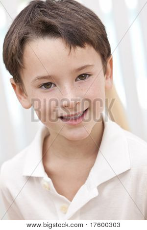 Head shot portrait of a happy smiling young boy in a white polo shirt