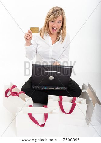 Exstatic young blond woman holding a credit card in front of a computer surrounded by shopping bags