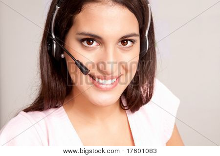 A female receptionist smiling at the viewer talking on the phone