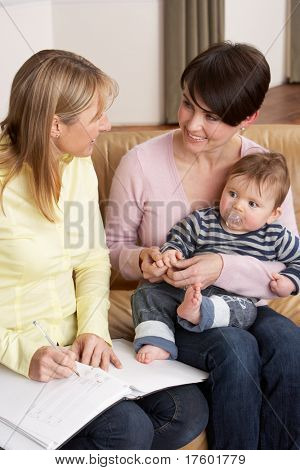 Mother With Baby Talking With Health Visitor At Home