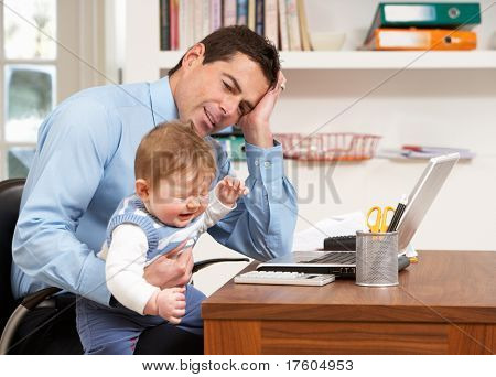 Stressed Man With Baby Working From Home Using Laptop