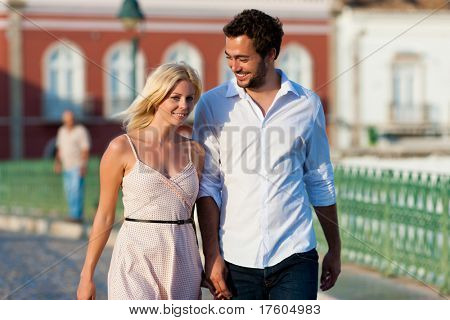 Couple having a city break in summer walking in the evening light