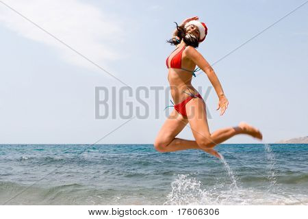 young sexy santa girl is jumping in the beach