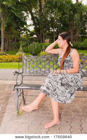 Asian Women Distracted On Bench In Park Faced Right