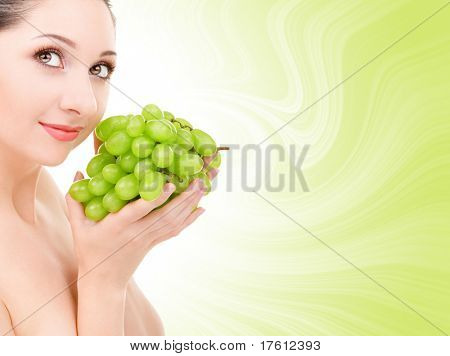 pretty woman with green grape isolated on the white background