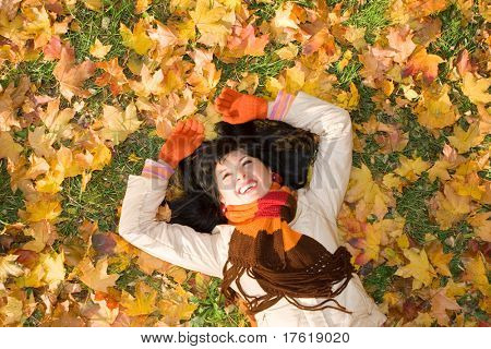 Young pretty woman on the autumn leaf