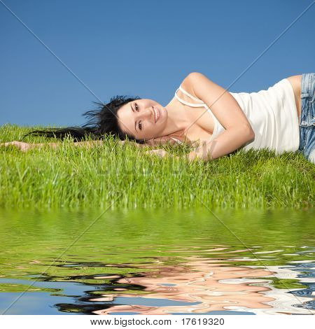 happy young woman rest on the green grass