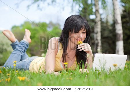 Cute woman with white laptop in the park with dandelions