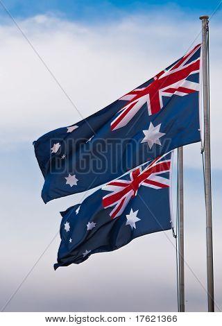 Twin Australian Flags Fly Against A Blue Sky