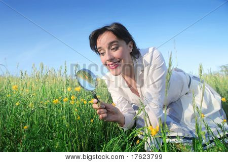 Smiling woman observing some flowers with a magnifying glass