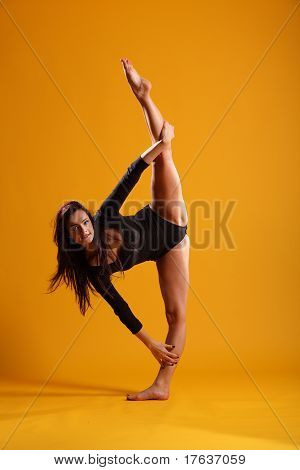 Side splits dance pose on yellow