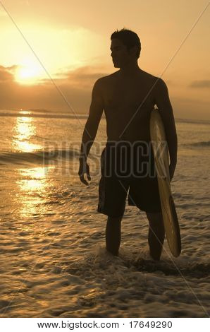 Surfer standing in surf, holding surfboard, at sunset