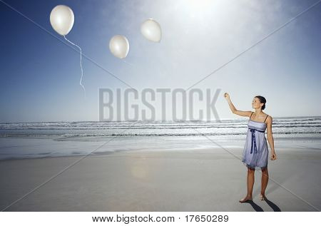 Woman letting balloons go on beach, elevated view