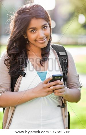A shot of an asian student texting with her cellphone on campus
