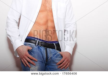 portrait of a young man with unbuttoned shirt over white wall