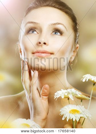 Skincare. Beautiful Spring Girl with Chamomile flowers. Healthy skin