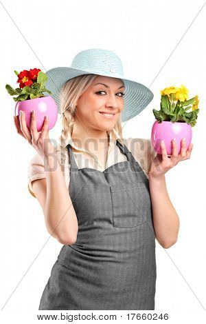 A smiling female gardener holding two potted plants isolated against white background