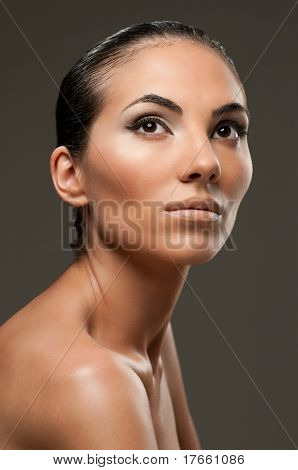Beautiful female model with professional fashion makeup posing over gray background