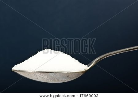 sugar on spoon on dark background