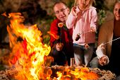 stock photo of boy scout  - Family at the barbecue in the evening - JPG