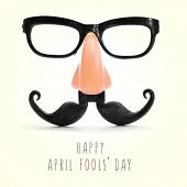 fake eyeglasses, nose and mustache and the text happy april fools day in a beige background, with a  poster