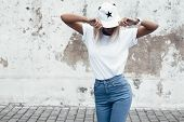 Hipster girl wearing blank white t-shirt, jeans and baseball cap posing against rough street wall, m poster