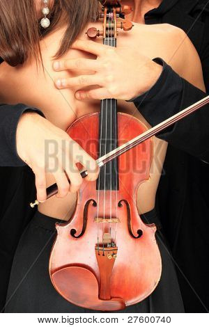 Beautiful sensual couple with violin over black background