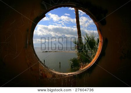 Looking out a round window to the sea.