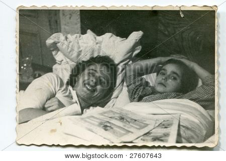Vintage photo of mother and daughter in bed (fifties)