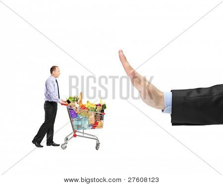 Man pushing a shopping cart full food ingredients and a hand gesturing stop isolated on white background