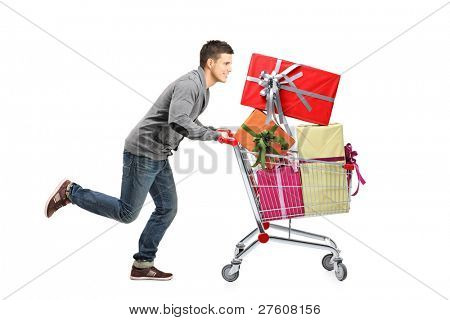 Young man running and pushing a shopping cart with gifts isolated on white background