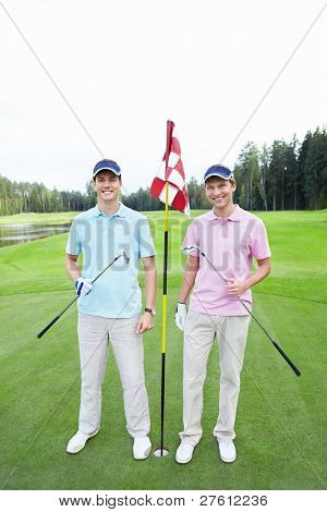 Two players at the hole on the golf course