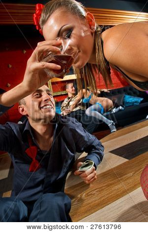 Man giving glass of whisky to stripteaser woman on stage