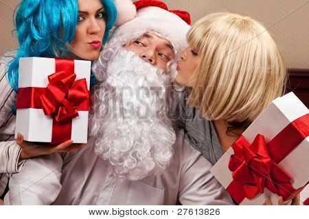Cheery party of two girls with Santa Claus